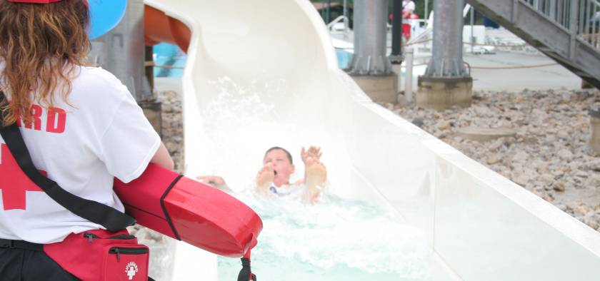 Lifeguard watching a child coming down water slide